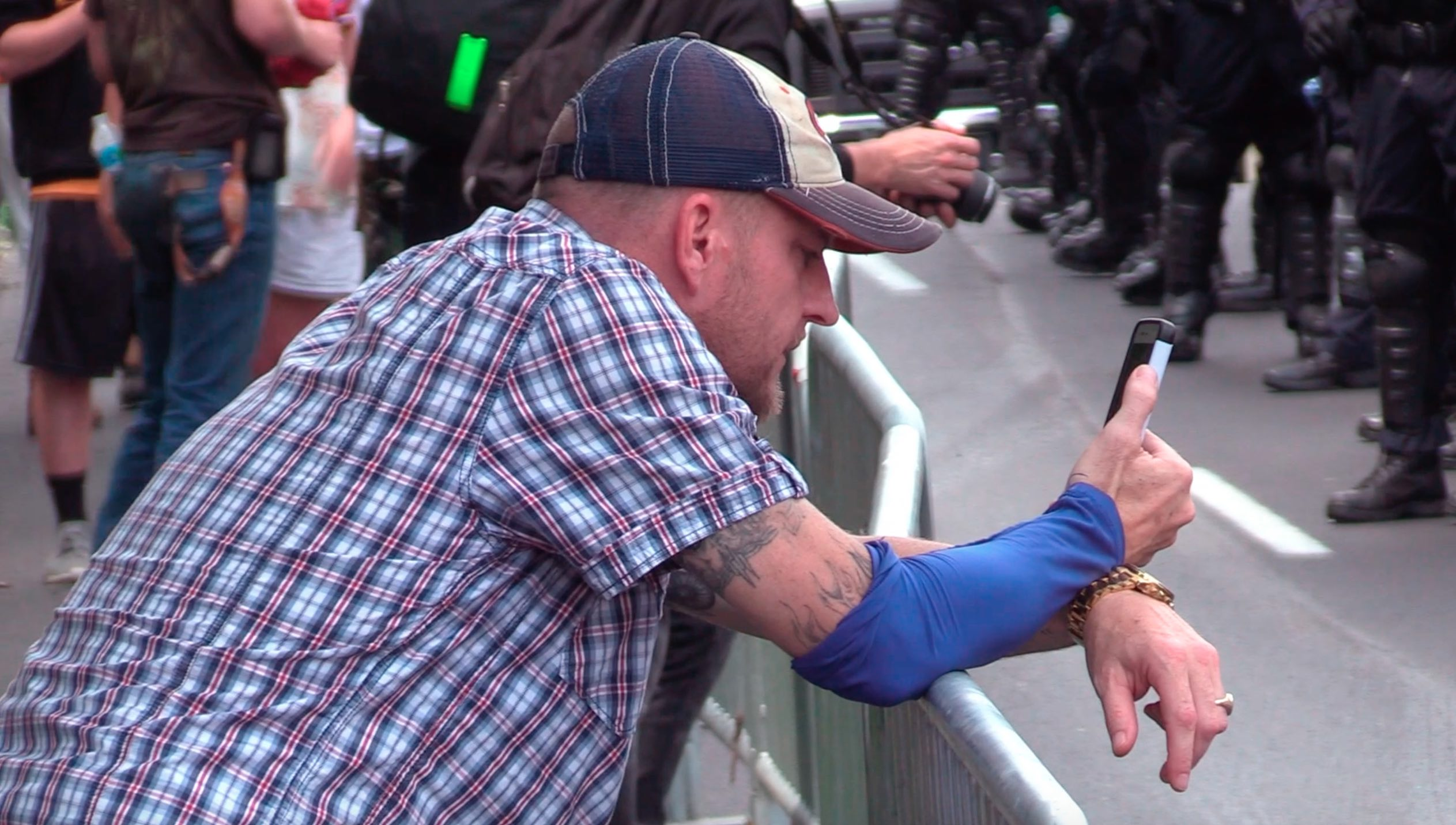 Anti-racist protesters offered this man $1,000 cash to remove his blue armband to prove he wasn't covering a neo-Nazi tattoo. He refused.
