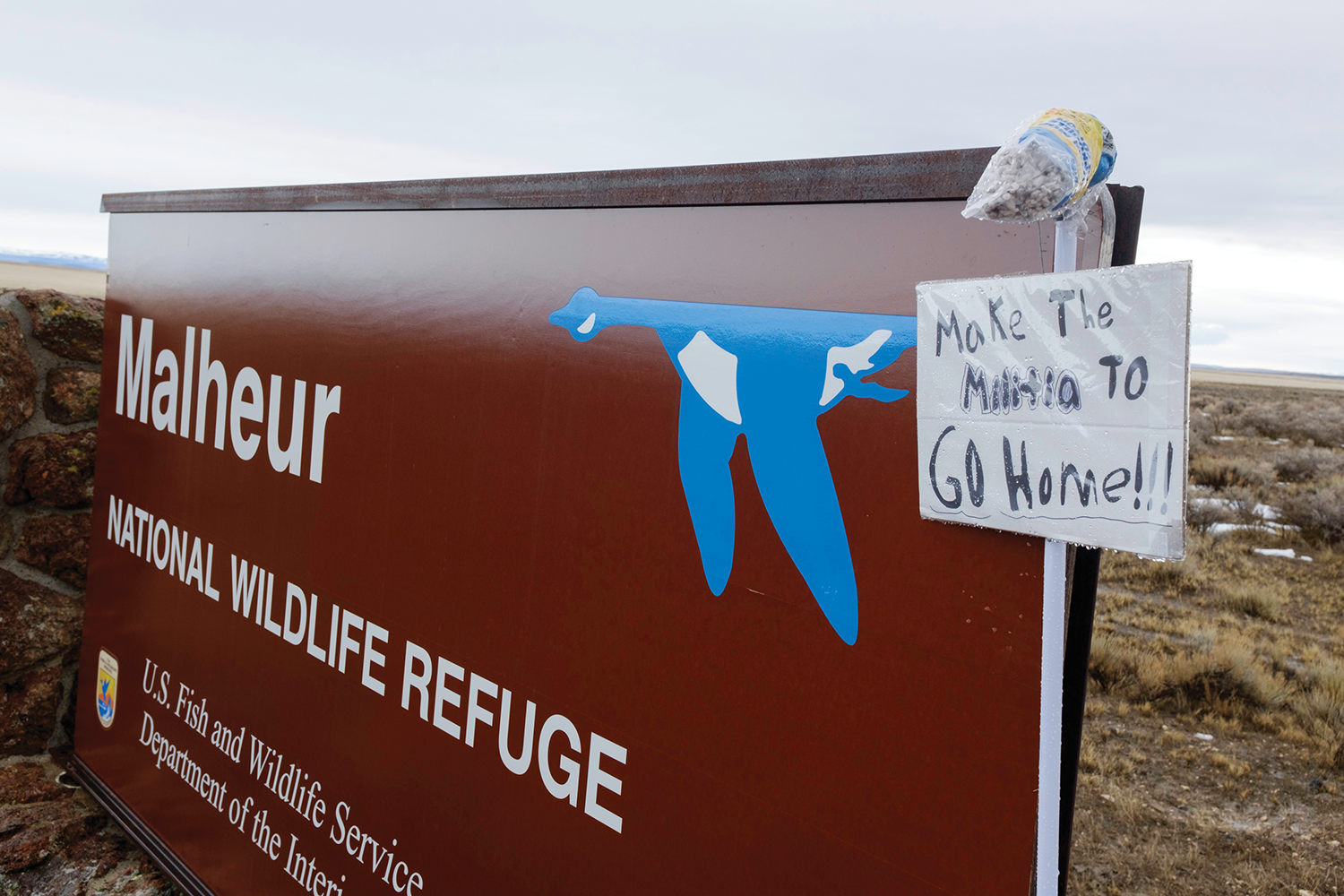 "Malheur National Wildlife Refuge sign that has been covered with another sign that says ""Make the Militia Go Home"""
